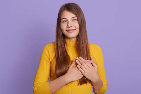 Friendly woman has heart filled with love and gratitude, keeps both hands on chest, has lovely sincere smile, wears yellow sweater, stands against purple background.