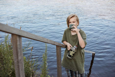 Blond little boy drinking hot tea from over river, male child spending time in open air, wearing green t shirt, enjoying hot beverage while posing near water. 스톡 콘텐츠