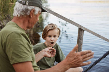 Successful fishing, dad telling about big fish to catch during summer weekend, mature man fly fishing, fisherman with grandson, son looking at father with opened mouth and astonished facial expression