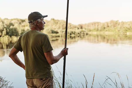 Senior fisherman catches fish, standing with fishing rod near water, looking in distance, wearing t shirt and cap, elderly man relaxing and enjoying beautiful nature. 스톡 콘텐츠