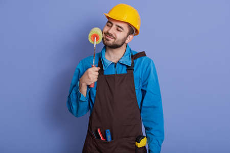 Decorator with paint roller in hands touching his beard and keeps eyes closed, guy wearing helmet and brown apron, labor posing isolated over blue background. Banco de Imagens