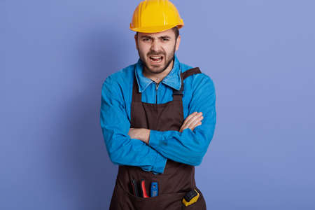 Annoyed emotional workman wearing yellow protective construction helmet, shirt and brown apron, has much work to do, scream with stress and panic, keeps arms folded.
