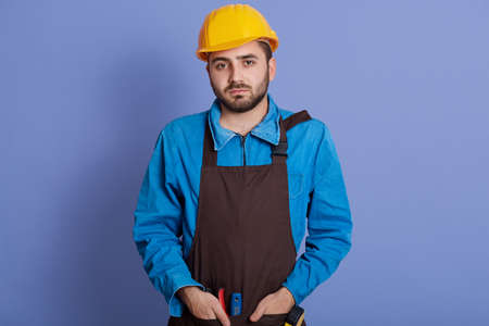 Serious man does redecoration at home, wears protective helmet and brown apron, poses indoor against blue wall, busy with repairing and renovation, has upset facial expression. Banco de Imagens