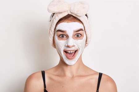 Excited woman wearing head band with bow looking directly at camera with astonished facial expression, lady looks surprised, stands with big eyes.
