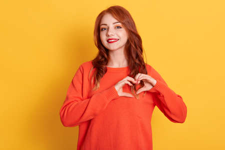 Portrait of lovely red haired female model makes heart gesture, demonstrates love sign, has happy expression, wearing orange sweater, posing against yellow background. Foto de archivo