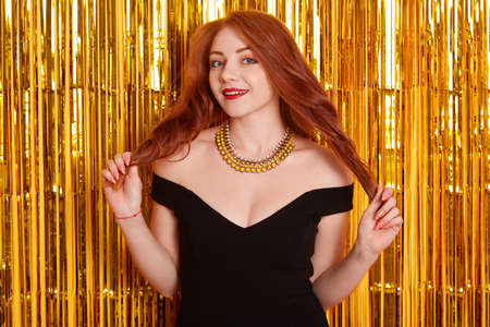 Happy red haired female with red lips looking at camera with flirting facial expression, touching her curls, wearing black dress and necklace, stands over decorated with golden tinsel wall.