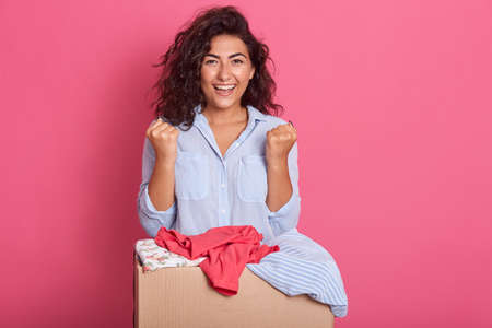 Positive attractive cute volunteer looking directly at camera and clenching fists, posing near paper box with donated clothes for charity organizations, lady wearing casual shirt.