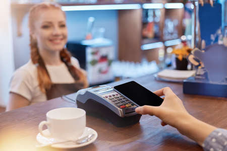 Unknown woman paying for coffee by mobile phone in restaurant, white cup of coffee on brown counter, red haired smiling barista on background, faceless customer with phone in hands. 免版税图像