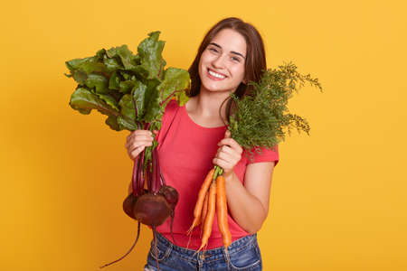 Portrait of smiling female gardener with carrot and beetroots in hands, looking smiling at camera, girl vegetarian wearing casual red t shirt against yellow wall.
