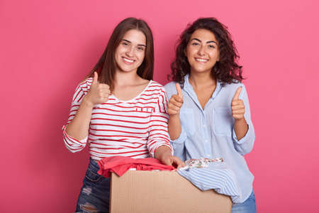 Smiling young women posing near box full of clothes, showing thumb up recommend donating apparel to needy people, happy females stack good things in charity package, clothing for reuse. 免版税图像
