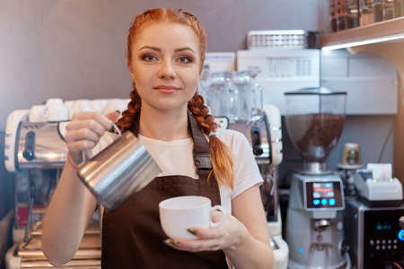 Barista preparing traditional boil Turkish coffee, red haired waitress wearing white t shirt and brown apron, looking smiling directly at camera, lady with pig tails.