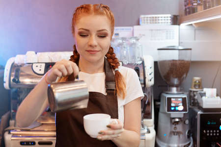 Red haired barista girl brews coffee from turk in coffee shop, concentrated woman working in cafe, lady in white t shirt and brown apron with coffee machine in background.
