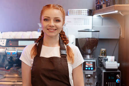 Red haired barista posing in cafe shop, wearing white t shirt and brown apron, standing with coffee machine on background, looking smiling at camera.