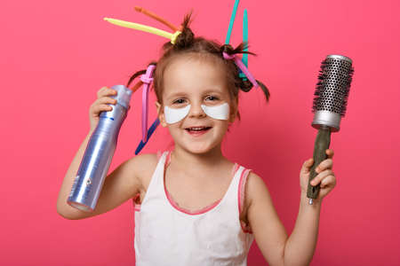 Smiling girl wearing white t shirt, has colored curlers on her hair, holding com and hairbrush, looking smiling at camera, charming female child preparing for party. 免版税图像