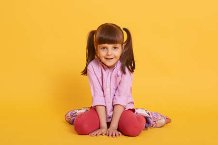 Cute girl sits in rollers in shirt and leggins and smiles, having two ponytail, looks happy, posing isolated over yellow background, funny female child. 免版税图像