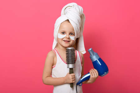 Beautiful cute girl with blue hair dryer and comb in hands, has white towel on head and patches under eyes, charming fashion monger posing isolated over pink background. 免版税图像