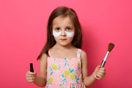 Charming serious little girl with brush and pomade in hands, wants to do make up with mother's cosmetic, posing with patches under her eyes, wears dress, standing isolated over pink wall. 免版税图像