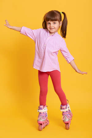 Pleasant looking kid raising hands while wearing roller skates, having two ponytails, standing isolated over yellow background, having fun and looks at camera.