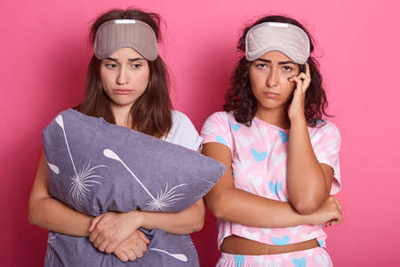 Two dark haired sleepy ladies with sleeping mask on foreheads, standing with pillow in hands, expressing sadness, stands with pout lips against pink wall.