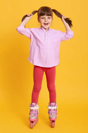 Little girl roller skating against yellow background, wearing shirt and leggins, touching her hair, looking directly at camera, cute female child having fun.