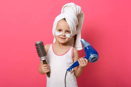 Smiling cute child wearing t shirt and white towel posing against rosy wall, small lady with comb and hair drier, little girl with patches under eyes. 免版税图像