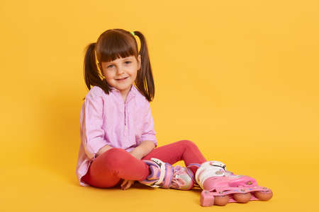 Smiling little kid with two funny ponytail looking directly at camera wit happy look, wearing leggins, shirt and roller skates, sitting on floor against yellow wall.