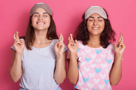 Two pretty women in pajamas and blind fold praying with crossed fingers, keep eyes closed, standing against pink wall, ladies with toothy smiles, wearing pajamas.