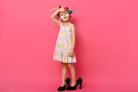 Cute little girl posing isolated over rosy background, wearing dress and mother's shoes, looks tired, stands with patches under eyes and colored curlers, keeping hand on forehead.