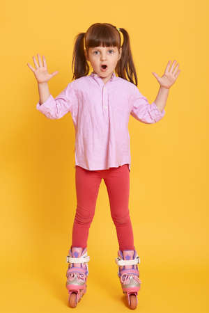 Astonished female child with raising hands, looks at camera with widely opened mouth, kid wearing shirt and leggins, shocked little girl in roller skates against yellow wall.
