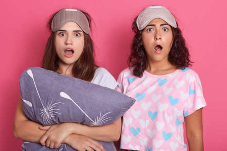 Astonished young female standing with widely opened mouths, expressing astonishment, wearing pajamas and sleeping mask, hold gray pillow isolated over rosy background.