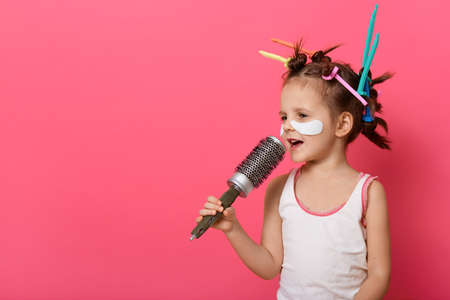 Side view of little girl with colored curlers, preparing for kinder garden holiday, singing songs and imagines she holds microphones, copy space for advertisement.