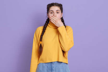 Young beautiful brunette woman wearing casual yellow sweater, posing over lilac background, being shocked, female covering mouth with hands for mistake.