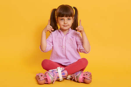 Dark haired little girl wearing roller skates, shirt and leggins, looking directly at camera and pointing up with fore fingers, sitting with crossed legs against yellow wall. 免版税图像