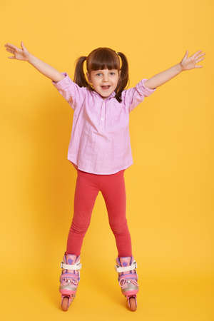 Happy little girl in shirt and leggins with roller skates posing indoors with hands up, standing against yellow background, cute kid looks excited and gladness. 免版税图像