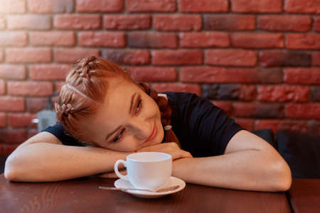 Beautiful woman with cup of coffee lies on table and looking smiling aside, tired student has break, posing against brick wall in black wall, red haired lady resting in cafeteria. 免版税图像