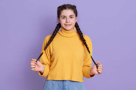 Pleasant looking cheerful Caucasian girl keeps both hands on her pigtails, wears yellow stylish sweater, posing isolated over lilac background, charming woman.