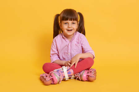 Little charming cute girl with roller skates sitting on floor with crossed legs, looks at camera, female child with two ponytail isolated over yellow background.