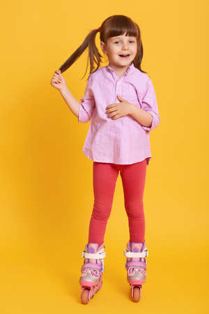 Smiling happy female posing isolated over yellow background, wearing leggins and casual shirt, kid touching her ponytail, look sat camera, child roller skating.