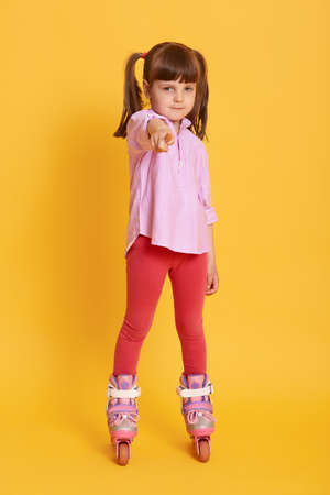 Charming female child in roller skates looking and pointing to camera with fore finger, kid wearing shirt and leggins, has two ponytail, posing against yellow background. 免版税图像