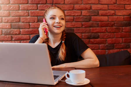 Young woman talking on phone while working online via laptop in cafe, sitting at table and drinking coffee, posing against brick wall, wearing black casual t shirt.
