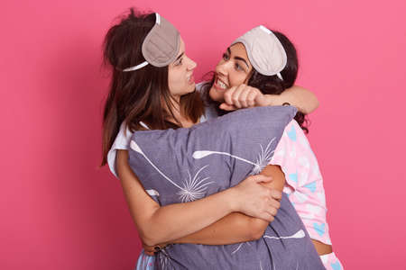 Two friends fighting during pajamas party, female embracing gray pillow, girl with gray blindfold choking her girlfriend, women standing against pink background.
