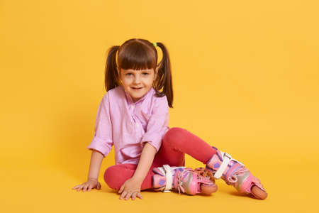 Cute little girl with happy facial expression looks smiling at camera, going to roller skate, active lifestyle for kids, summer leisure time, female kid with two ponytails. 免版税图像
