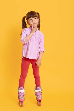 Pleasant pretty kid standing in skates, looking directly at camera, spending time in active way, having pensive facial expression, keeping finger on her cheek. 免版税图像