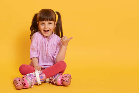 Happy girl in roller skating sitting on floor against yellow background showing thumbs aside with excited facial expression, copy space for advertisement or promotion.