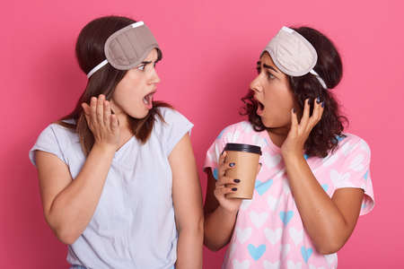 Two astonished dark haired females with widely opened mouths, girls hear shocking news, wearing pajamas and blindfold, standing with surprised expressions over rose background.