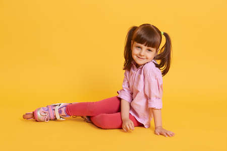 Little cute Caucasian woman with roller skates on floor, charming female kid with ponytails, wearing shirt and leggins, posing isolated over yellow background.