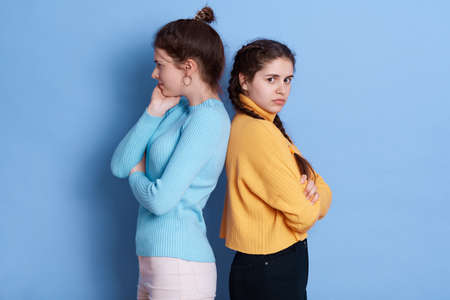 Two European girls going through conflict in their relationship, posing back to back isolated over blue background, keeping hands folded, wearing casual outfits.