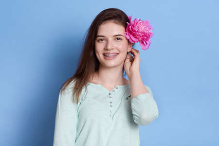 Portrait of young female with rose flower behind ear isolated over blue background, brunette lady wearing casual shirt, looking smiling directly at camera.