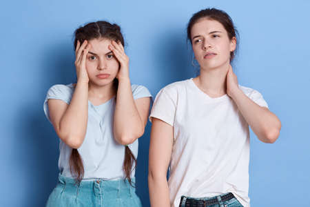 Thinking, tired or ill females with headache, young women touching her temples and neck, wearing white casual t shirts, standing isolated over blue background.