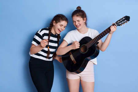 Winsome ladies with knot and pigtails singing songs and playing guitar, having fun together, preparing for music competition, posing isolated over blue background. 免版税图像